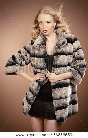 Fashion shot of a beautiful blonde woman wearing jewelry and fur coat. Studio shot.
