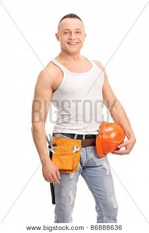 Vertical shot of a handsome construction worker holding an orange helmet and wearing a tool belt isolated on white background