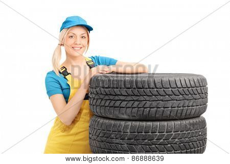 Female mechanic with a blue cap leaning on a stack of used tires isolated on white background