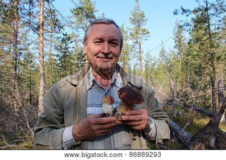 Man with two cepes mushrooms in the forest