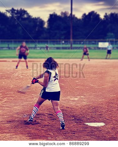 a young girl batting a ball at home plate in a softball game toned with a retro vintage instagram filter