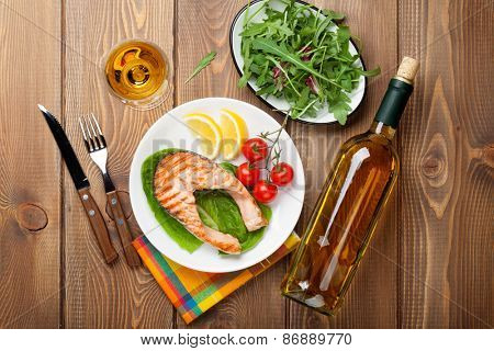 Grilled salmon and whtie wine on wooden table. Top view