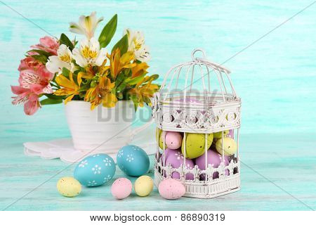 Easter composition with Easter eggs in decorative cage and flowers, on color wooden background