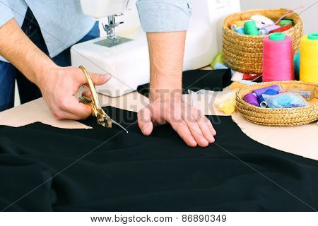 Male dressmaker cut fabric on table close-up