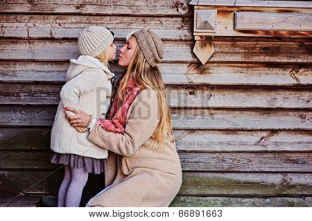 mother kisses her daughter on the walk