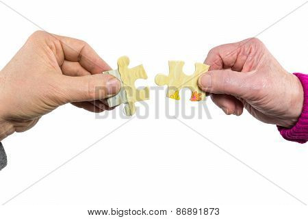 Two hands uniting fitting puzzle pieces