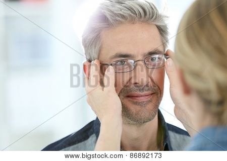 Mature man in optical store trying eyeglasses on