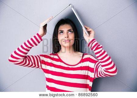 Beautiful woman holding laptop above her head like a roof over gray background. Looking up on laptop.