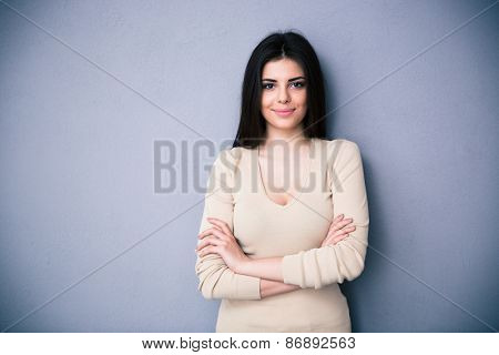 Portrait of a happy charming woman with arms folded posing over gray background. Wearing sweater. Looking at camera