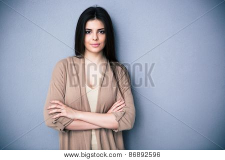 Portrait of attractive young woman with arms folded standing over gray background. Looking at camera