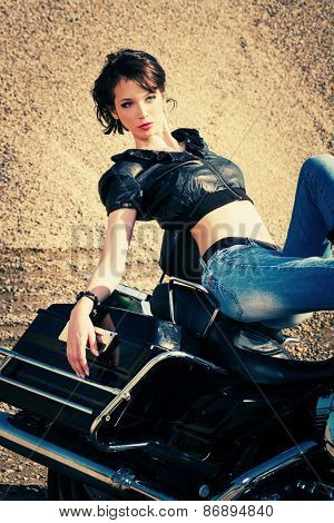 young beautiful woman sitting on motorbike, sunny day outdoor, sand in background