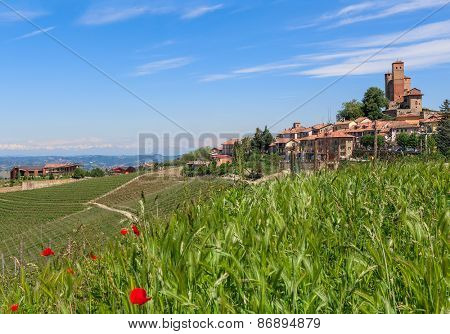 Red poppies among green grass and small town with medieval castle on background under blue sky in Piedmont, Italy.