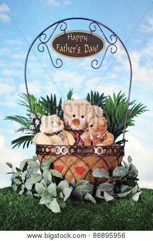 Toy bears -- father, son and daughter snuggled together within a foliage-filled wire basket on a grassy knoll with sky in the background..  A