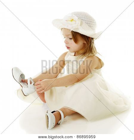 A beautiful, dressed up preschooler putting on her own white shoes.  On a white background.