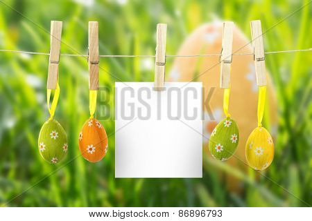 hanging easter eggs against easter egg nestled in the grass