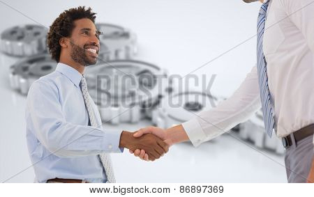 Two businessmen shaking hands in office against cogs and wheels
