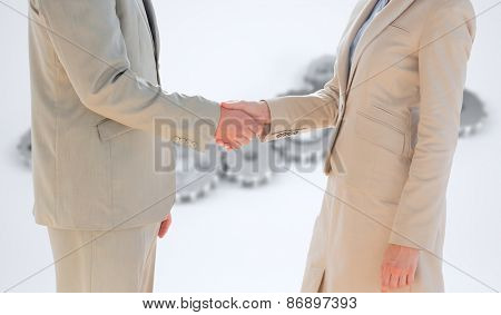 Business people shaking hands against cogs and wheels