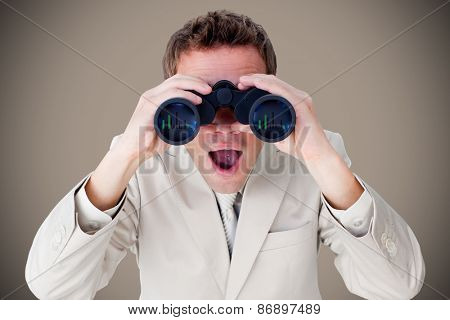 Positive businessman using binoculars against grey background with vignette
