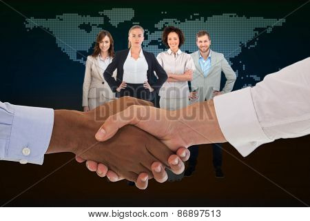 Close-up shot of a handshake in office against blue world map