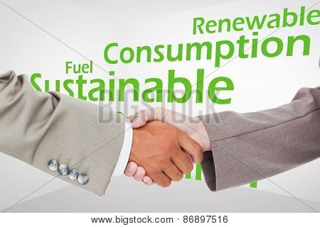 Side view of shaking hands against creative image of green economy concept
