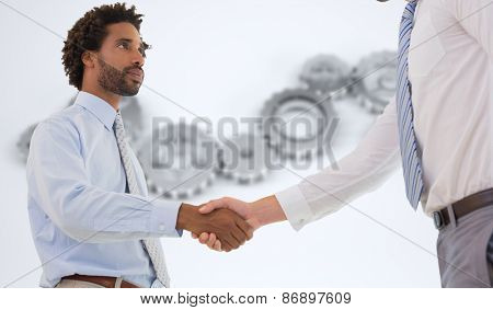 Young businessmen shaking hands in office against cogs and wheels