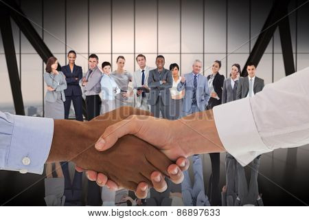 Close-up shot of a handshake in office against room with large window looking on city