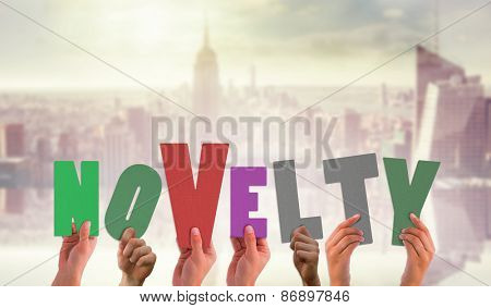 Hands holding up novelty against room with large window looking on city