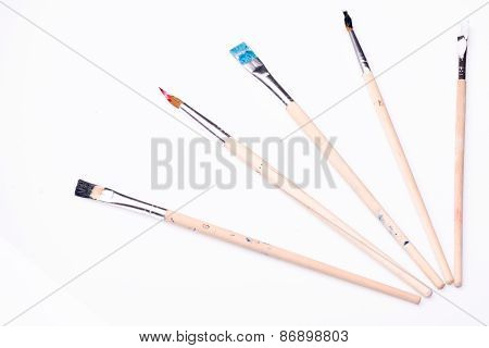 Five paintbrushes on a white background