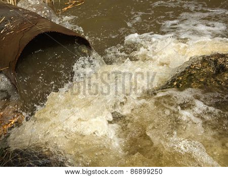 Waste Water Running Slow From A Concrete Pipeline Direct Onto A Natural Pond With Green Grass On The