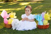 stock photo of baby easter  - Cute happy smiling little baby girl in white dress with white rabbit near wicker basket with Easter chocolate eggs in park on green grass - JPG