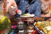 stock photo of vodka  - Person pouring vodka in the asian restaurant - JPG