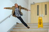 picture of slip hazard  - African American businessman falling on stairwell with yellow warning sign on steps - JPG