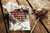 stock photo of chocolate spoon  - Bar of chocolate in foil with coffee beans in spoon on wooden table - JPG