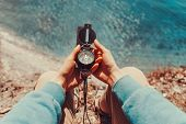 image of pov  - Traveler woman searching direction with a compass on coastline near the sea - JPG