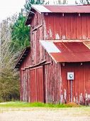 stock photo of red barn  - Empty old wooden red barn on a field - JPG