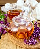 stock photo of oregano  - Herbal tea in a glass teapot and cup - JPG