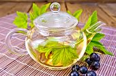 stock photo of black tea  - Tea in a glass teapot with leaves of black currant - JPG