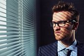 image of blind man  - Confident young businessman in eyeglasses looking through venetian blinds - JPG