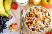 picture of cereal bowl  - Bowl of cereal with fruit on a white wooden table and fresh fruits behind top view - JPG