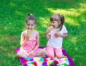 stock photo of tease  - Girls kids sisters friends teasing sitting on grass eating ice cream - JPG