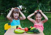 stock photo of tease  - Two happy girls kids children wearing beautiful dresses holding chives as ears above heads and teasing showing off their tongue - JPG