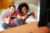 stock photo of pajamas  - Young Couple In Pajamas Playing Video Game Together - JPG