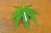 stock photo of joint  - Photo of cannabis leaf and joint on a wooden table - JPG