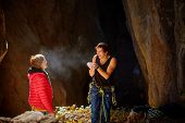stock photo of cave woman  - couple of  climbers standing in a cave - JPG