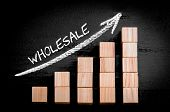 image of ascending  - Word Wholesale on ascending arrow above bar graph of Wooden small cubes isolated on black background - JPG
