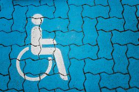 stock photo of handicapped  - International handicapped symbol painted in white on blue pavement parking space - JPG