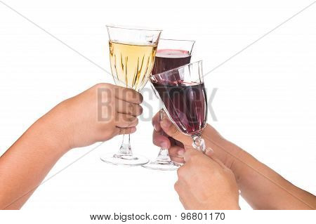 Hands toasting red and white wine in crystal glasses