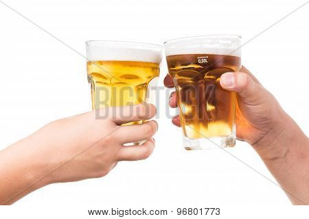 Two hands toasting and knocking refreshing cold beer glasses