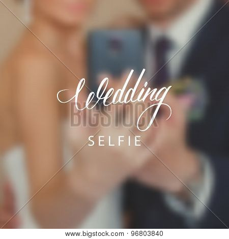 Wedding day typography element on blurred background. Bride and groom taking a selfie with a mobile