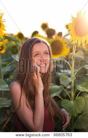 Young girl talking on the phone on among sunflowers at sunset